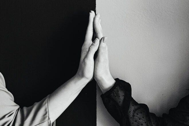 Zwei Hände vor einer schwarzweiß kontrastierter Wand